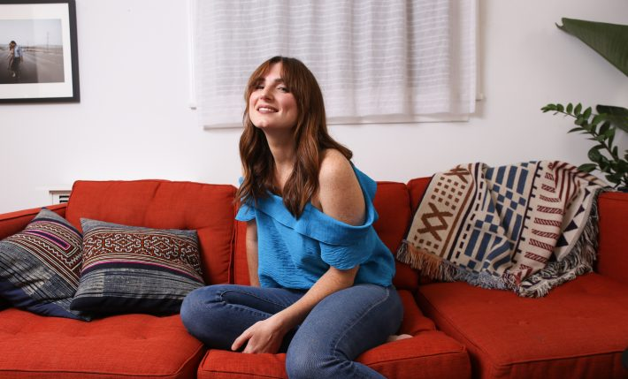 Florence Hartigan laughing on her red sofa in Los Angeles.